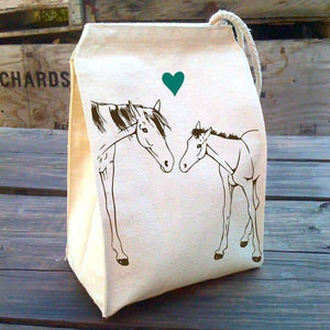 An ivory colored lunch bag with an illustration of two horses and a green heart.