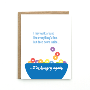 "A white card with a text: ""I MAY WALK AROUND LIKE EVERYTHING'S FINE. BUT DEEP DOWN INSIDE...I'M HUNGRY AGAIN"" and an illustration of a blue bowl of cereal. Comes with a brown envelope."