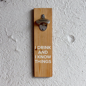 "Wooden bottle opening with white text ""I DRINK AND I KNOW THINGS."""