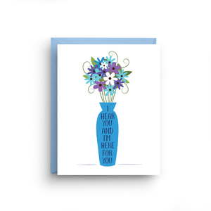 "A white card with a text: ""I HEAR YOU AND I'M HERE FOR YOU"" and an illustration of a blue flowers in a blue vase."" Comes with a light blue envelope."