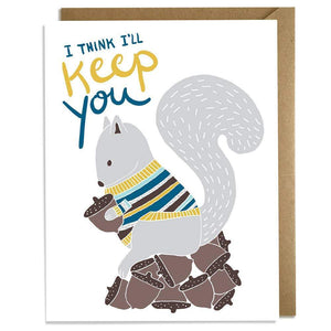 "A white card with text: ""I THINK I'LL KEEP YOU"" and an illustration of a grey squirrel holding an acorn. Comes with a brown envelope."