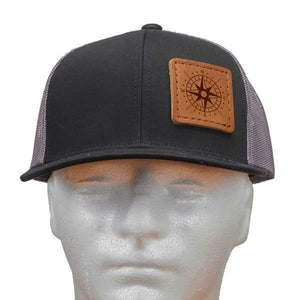 Black and grey netted hat with a brown leather patch with an illustration of a maroon compass.