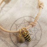 Tan colored leather wrap bracelet with a sphere and golden pine cone talismans.