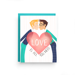 "A white card with text: ""LOVE IS ALL YOU NEED"" and an illustration of two men kissing. Comes with a teal envelope."