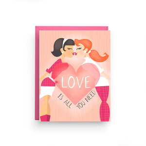 "A peach colored card with text: ""LOVE IS ALL YOUR NEED"" and an illustration of two women kissing. Comes with a pink envelope."