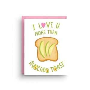 "A white card with lime colored text: ""I LOVE U MORE THAN AVOCADO TOAST"" and an illustration of an avocado toast. Comes with a pink envelope."