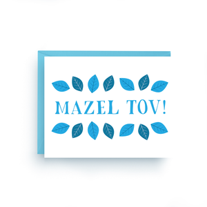 "A white card with a blue text: ""MAZEL TOV!"" and an illustration of blue leaves. Comes with a blue envelope."
