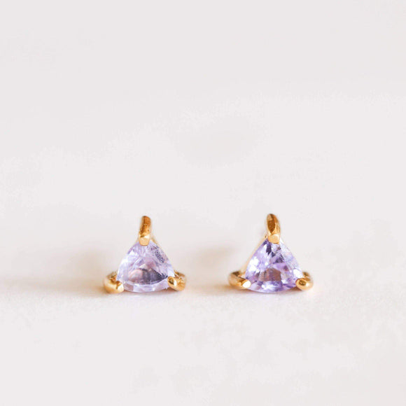 A pair of triangle shaped earrings made transparent lavender gem held by three golden plated edges.