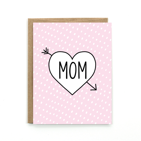 A polka dotted baby pink card with a heart and an arrow across the text:
