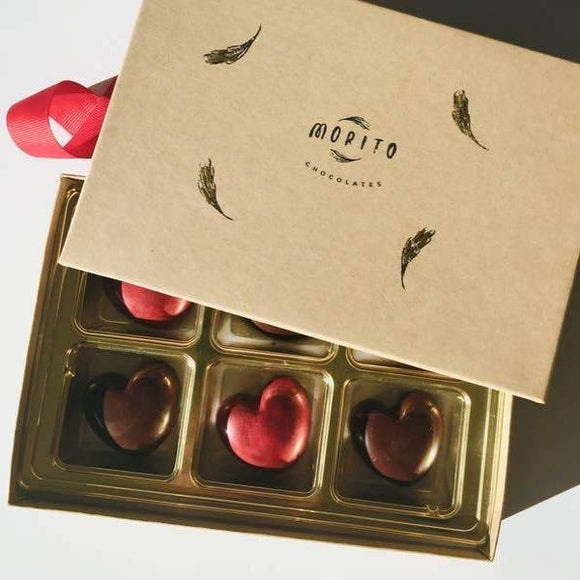 A box of heart shaped chocolates in brown and red colors.