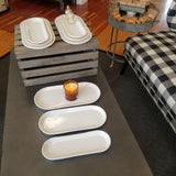 A set of long white stoneware nesting trays in three different sizes.