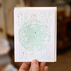"A white card with a mint text: ""OUT LOVE GROWS LIKE WILD FLOWERS"" and an illustration of wild flowers."