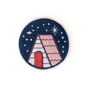 A round sticky pach with an illustration of a cabin under the stars.