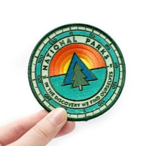 A round patch with an illustration of sunrise and a tree.