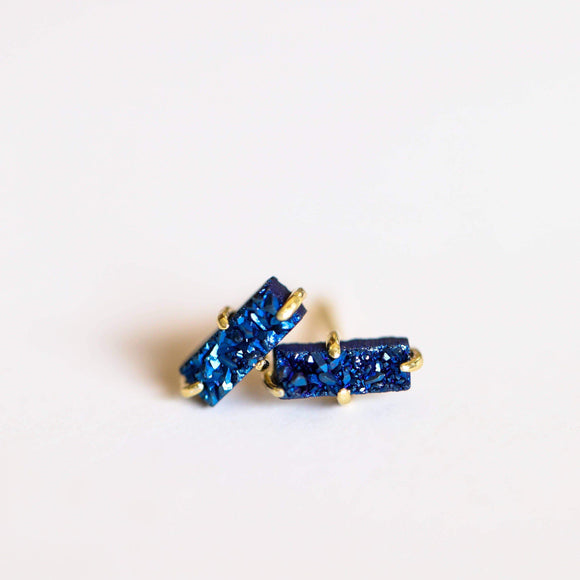 A pair of blue bar shaped druzy earrings.