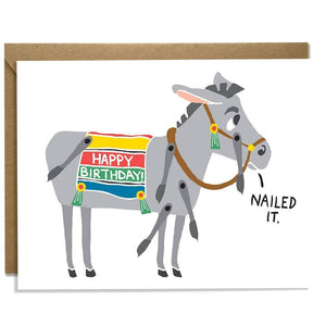 "A white card with a text: ""HAPPY BIRTHDAY"" and an illustration of a donkey saying ""nailed it."" Comes with a brown envelope."