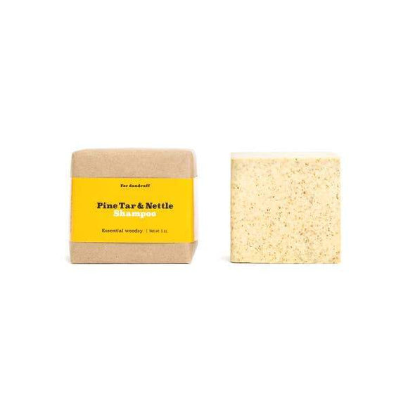 Two beige colored square pine tar and nettle shampoo bars.
