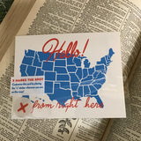"A white postcard with red text: ""HELLO FROM RIGHT HERE"" and an illustration of map of the US map. Comes with ""X"" stickers to mark state the card is coming from."