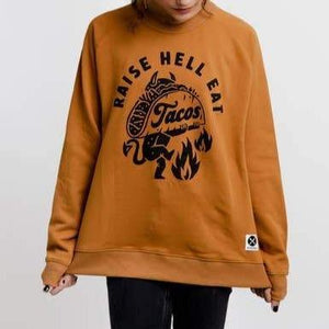 "A light brown sweatshirt with a black text: ""RAISE HELL EAT TACOS"" with an illustration of a devil holding a taco."