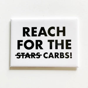 "A white square magnet with black text: ""REACH FOR THE (crossed out STARS) CARBS!"""