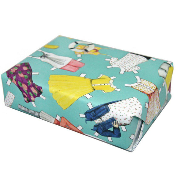 A present wrapped in a blue wrapping paper with an illustration of paper doll outfits.