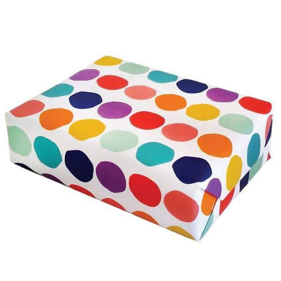 A present wrapped in a white wrapping paper with colorful polka dot patterns.
