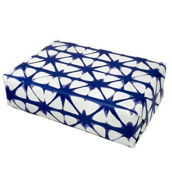 A present wrapped in a white wrapping paper with blue shibori patterns.