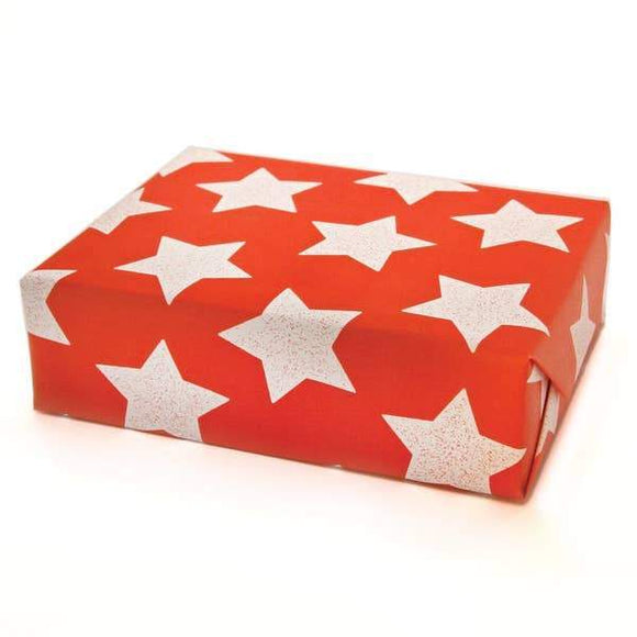 A present wrapped in a red wrapping paper with illustration of white stars.