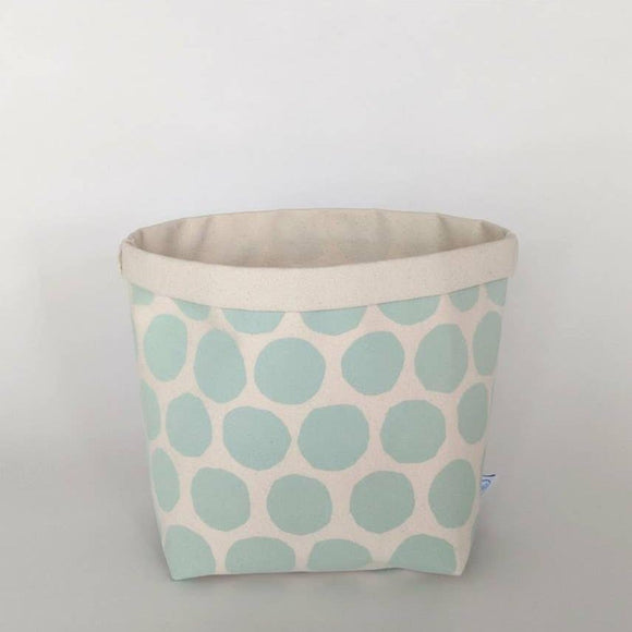 A canvas bin with sage circle patterns.