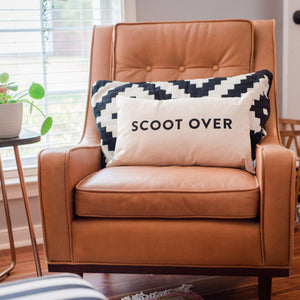 "A white square pillow with black text: ""SCOOT OVER."""