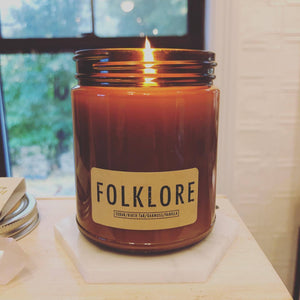 "A brown jar of ""FOLKLORE"" scent candle."