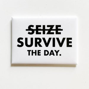 "A white square magnet with text: ""(SEIZE crossed out) SURVIVE THE DAY."""