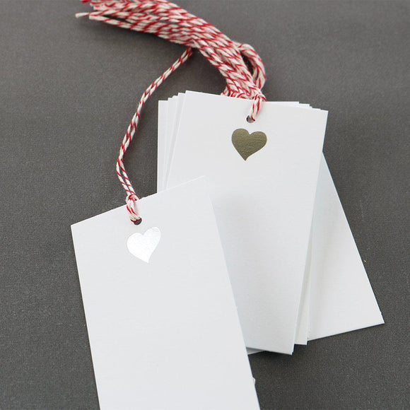 A white gift tag with red/white strings with an illustration of a silver heart on top.