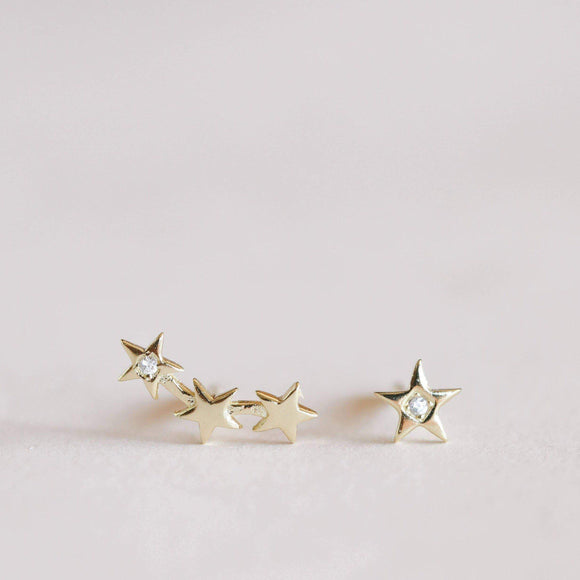 Pair of golden plated earrings with a cubic in the center; one in shape of three stars joined and one in shape of a star.