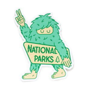 "Sticker of a green big foot holding a sign that reads ""NATIONAL PARKS."""