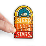 "An arc shaped sticker of a blue Bigfoot sleeping under a rainbow colored sheets with text: ""SLEEP UNDER THE STARS."""