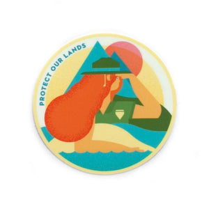 "A round sticker of an illustration of scenic view and  a girl with text:""PROTECT OUR LANDS."""