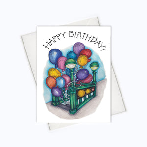 "A white card with a black text: ""HAPPY BIRTHDAY!"" and an illustration of a subway stairs decorated  with colorful balloons. Comes with a white envelope."