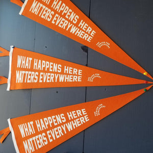 "An orange triangular pennant with white text: ""WHAT HAPPENS HERE MATTERS EVERYWHERE."""