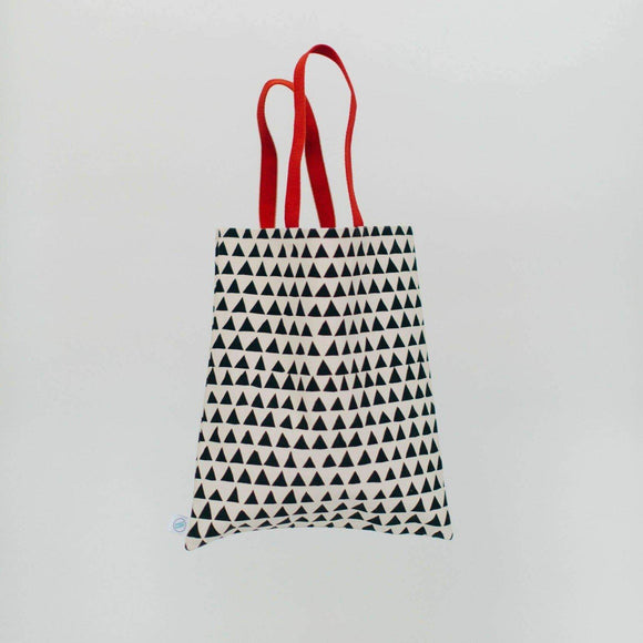 A white canvas tote bag with black triangle patterns and red handles.