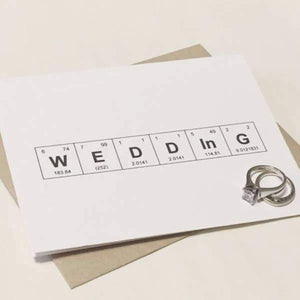 "A white card with a black text ""WEDDING"" in a periodic table design. Comes with a brown envelope."