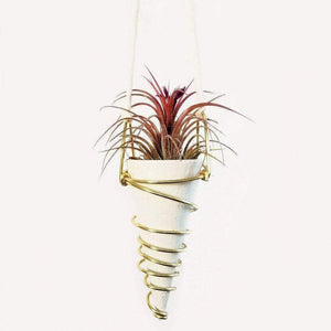 A white cone shaped hanging planter with copper details.