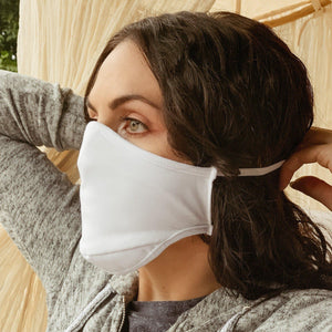 Woman with brown hair tying on a white face mask