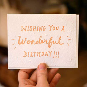 "A white card with an orange text: ""WISHING YOU A WONDERFUL BIRTHDAY!"""
