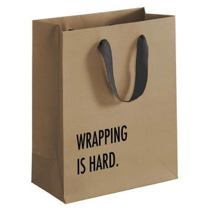 "A brown gift bag with a black text: ""WRAPPING IS HARD."""