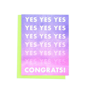 "A purple and pink ombre background card with white text: ""YES! CONGRATS!"" Comes with a lime green envelope."