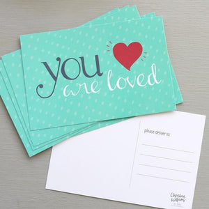 "A blue post card with polkadot background and a text: ""YOU ARE LOVED."""