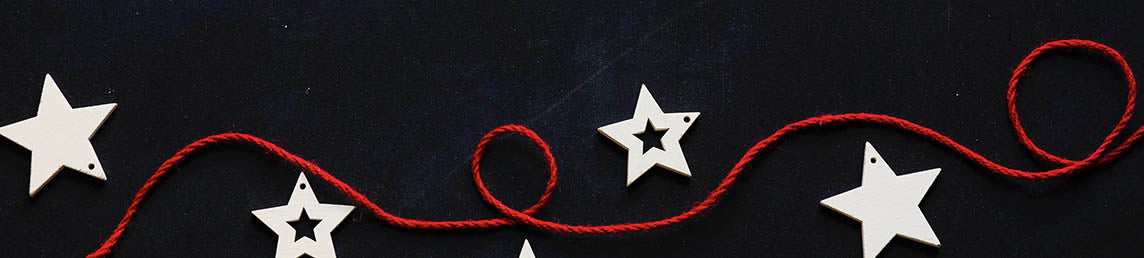 Red ribbon with white Christmas themed stars on a navy backdrop