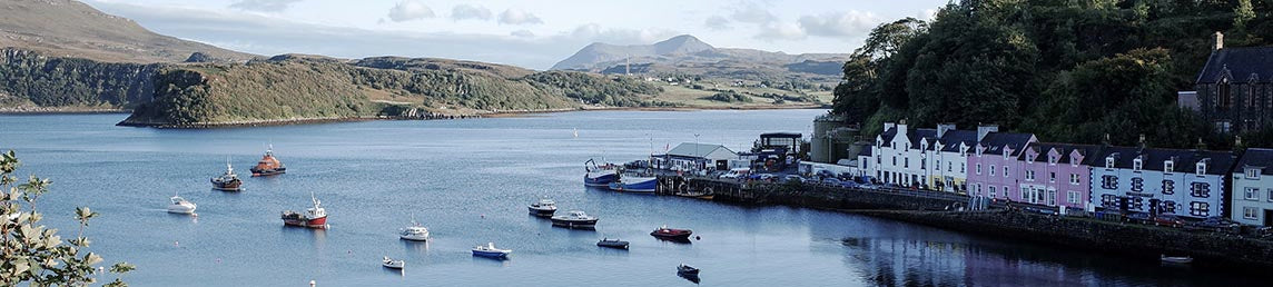 An image of Scotland, houses on a loch with boats, hills in the background