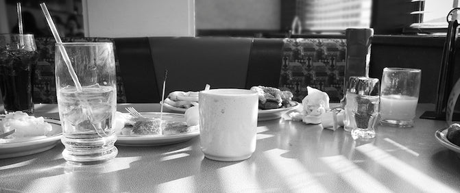 Black and white image of a dining table covered in dirty crockery